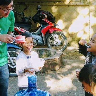 An intern gains dental work experience in Vietnam by teaching children how to brush their teeth during an outreach.